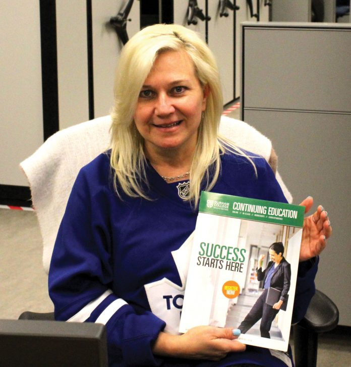Woman sitting with Durham College School of Continuing Education booklet.