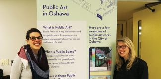 "Catherine Richards stands on the left of a large poster labelled ""Public Arts Master Plan. On the right is Marnie Mandel."