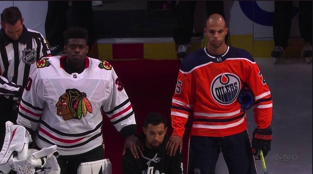 Malcolm Subban (left) and Darnell Nurse (right) show their support for Matt Dumba (middle) while he kneels for the Canadian and American national anthems.