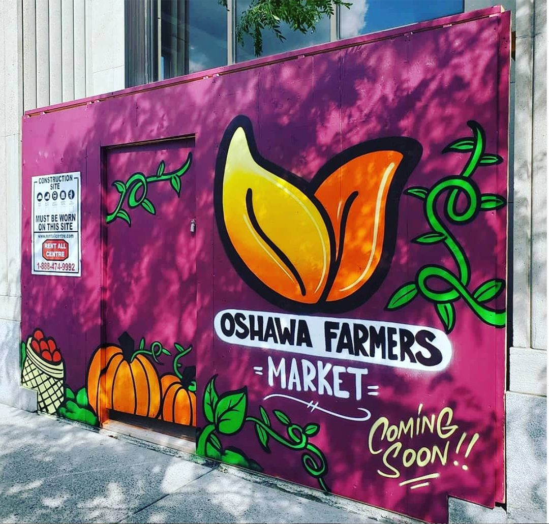 This is artwork outside the market that features pumpkins, apples, and autumn leaves.
