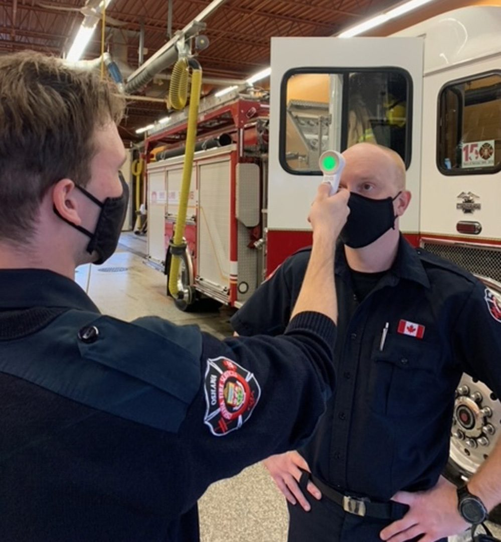 Firefighter Vestby getting his temperature checked by FIrefighter Kettrick at station 3 in Oshawa.