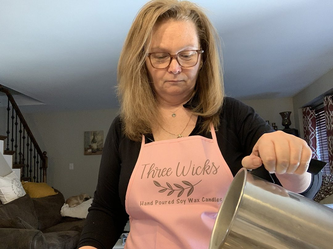 Diane Kennedy, owner of Three Wicks, pours soy wax into candle molds.